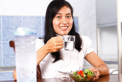 Smiling young woman drinking water with salad on table Royalty Free Stock Photo