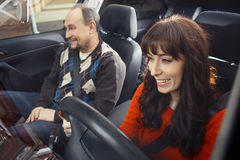 Smiling young woman driver with instructor on passenger`s seat. Father and daughter in car Stock Photography