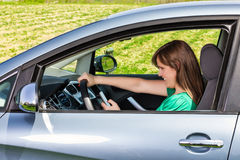 Smiling young woman driver reading/typing a text message Royalty Free Stock Photo