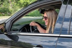 Smiling young woman driving black SUV with windows down royalty free stock image