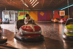 Smiling young woman driving a bumper car Royalty Free Stock Images