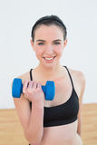 Smiling young woman with dumbbell at fitness studio Stock Images