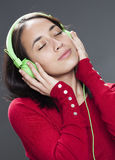 Smiling young woman with earphone relaxing to the sound of music. Listening to music concept - attractive 20s girl listening to music with headphone for Royalty Free Stock Photo