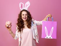 Smiling young woman with Easter shopping bag and piggy bank. Festive bunny and eggs season. smiling young woman in Easter bunny ears on pink background with stock image