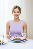 Smiling young woman eating appetizer at restaurant Stock Images