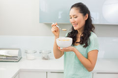 Smiling young woman eating cereals in kitchen Stock Images