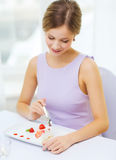 Smiling young woman eating dessert at restaurant Royalty Free Stock Image