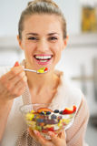 Smiling young woman eating fresh fruit salad Royalty Free Stock Images
