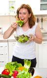 Smiling young woman eating fresh salad in modern kitchen stock images