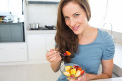 Smiling young woman eating fruit salad in kitchen Royalty Free Stock Images