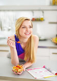 Smiling young woman eating fruits salad in kitchen Stock Image