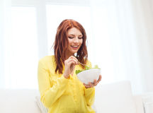 Smiling young woman eating green salad at home Royalty Free Stock Photography