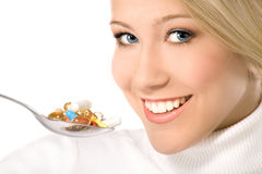 Smiling young woman eating a lot of pills on spoon. Beautiful smiling blond with blue eyes eating a lot of colorful pills on the spoon Royalty Free Stock Images