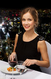 Smiling young woman eating main course Royalty Free Stock Photography
