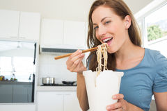 Smiling young woman eating noodles in kitchen Royalty Free Stock Photos