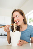 Smiling young woman eating noodles in kitchen Stock Images