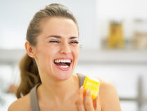 Smiling young woman eating pineapple slice Royalty Free Stock Image
