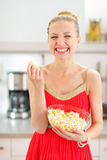 Smiling young woman eating popcorn in kitchen Royalty Free Stock Photo