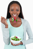 Smiling young woman eating salad. Against a white background Stock Photography