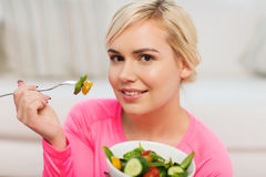 Smiling young woman eating salad at home Stock Photos