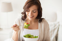 Smiling young woman eating salad at home stock photography