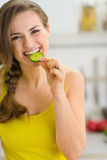 Smiling young woman eating slice of cucumber Stock Photos