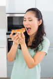 Smiling young woman eating a slice of pizza in kitchen Royalty Free Stock Photo