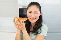 Smiling young woman eating a slice of pizza in kitchen Royalty Free Stock Image