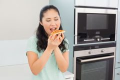 Smiling young woman eating a slice of pizza in kitchen Stock Photos