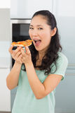 Smiling young woman eating a slice of pizza in kitchen Royalty Free Stock Photography
