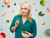 Smiling young woman eating vegetable salad Stock Photo