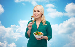 Smiling young woman eating vegetable salad Stock Photos