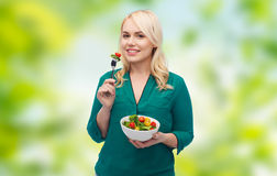 Smiling young woman eating vegetable salad Royalty Free Stock Images