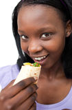 Smiling young woman eating a wrap Stock Photography
