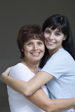 Smiling Young Woman Embracing Her Mother Stock Image