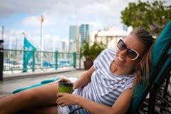 Smiling young woman enjoying coffee Royalty Free Stock Image