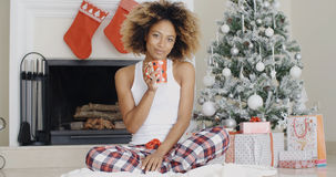 Smiling young woman enjoying a cup of Xmas coffee Royalty Free Stock Image
