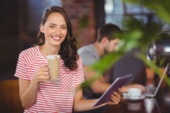 Smiling young woman enjoying latte and using tablet computer Royalty Free Stock Photos