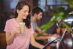 Smiling young woman enjoying latte and using tablet computer Stock Photo