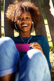 Smiling young woman enjoying music on smart phone Stock Images