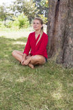 Smiling young woman enjoying summer freshness under a tree Royalty Free Stock Photos