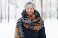 Smiling Young Woman Enjoying Winter. Waist up portrait of beautiful young woman in winter forest looking at camera and smiling, copy space royalty free stock photography