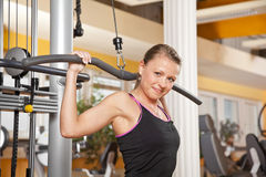 Smiling young woman exercising in gym. A smiling beautiful young woman in her twenties exercising in a fitness studio training her latissimus and looking into Stock Photo