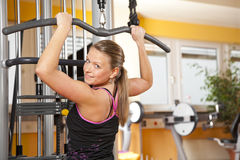 Smiling young woman exercising in gym. A smiling beautiful young woman in her twenties exercising in a fitness studio training her latissimus and looking into Royalty Free Stock Image