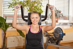 Smiling young woman exercising in gym. A smiling beautiful young woman in her twenties exercising in a fitness studio training her latissimus and looking into Royalty Free Stock Images