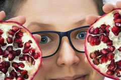 Smiling young woman with eyeglasses and pomegranate Royalty Free Stock Photos