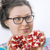 Smiling young woman with an eyeglasses and a pomegranate Royalty Free Stock Photo