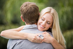 Smiling young woman with eyes closed while hugging man. Smiling young women with eyes closed while hugging men at resort Stock Image