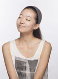 Smiling young woman with eyes closed, studio shot royalty free stock photography