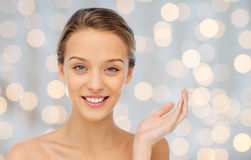 Smiling young woman face and shoulders. Beauty, people and health concept - smiling young woman face and shoulders over holidays lights background Stock Photo